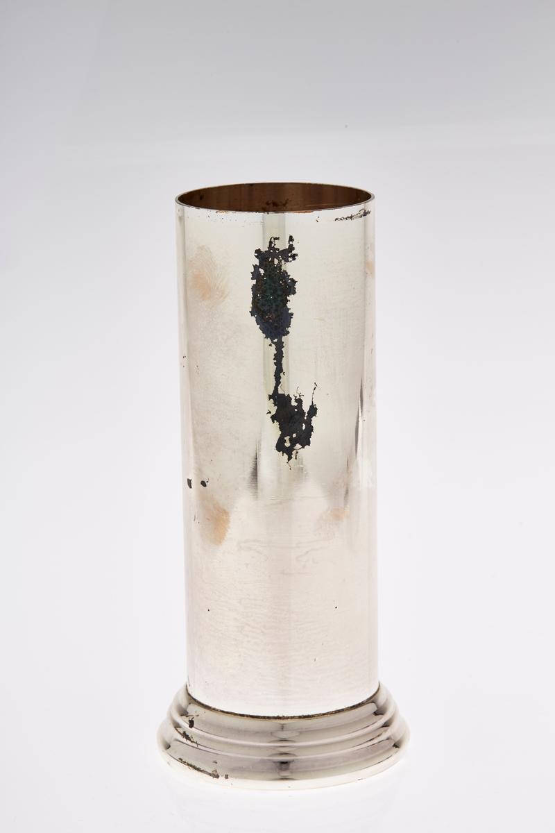 Sylinderformet pokal i metall. Har tilhørende lokk.