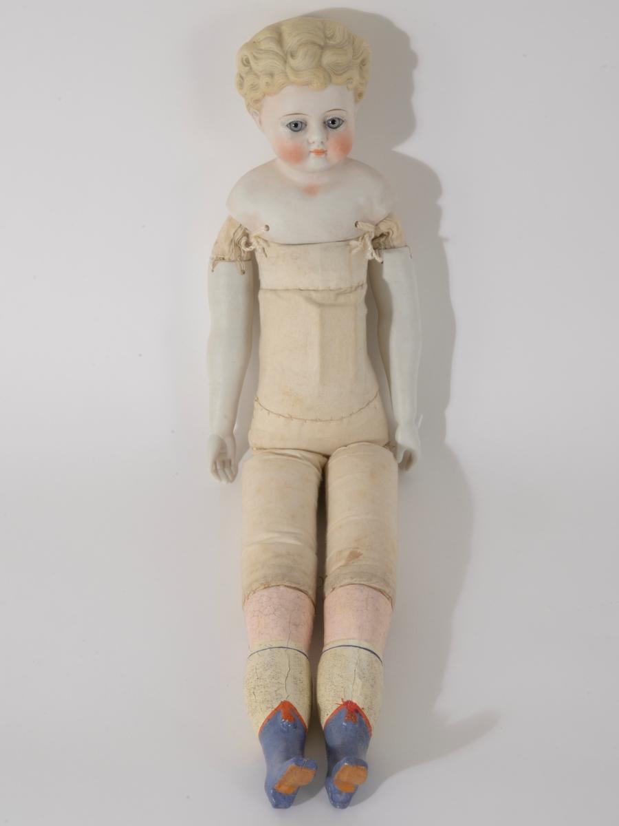 Porselenshode og armer. Pappmache ben, tøykropp. En firkantet gjenstand innsydd på magen.