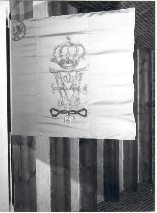 Rød silke med malt, hovedsaklig forgylt dekor: Fredrik IVs kronede speilmonogram med elefantorden. Norske løve i øvre hjørne ved fanestanden. Montert på fanestanden med spyd.