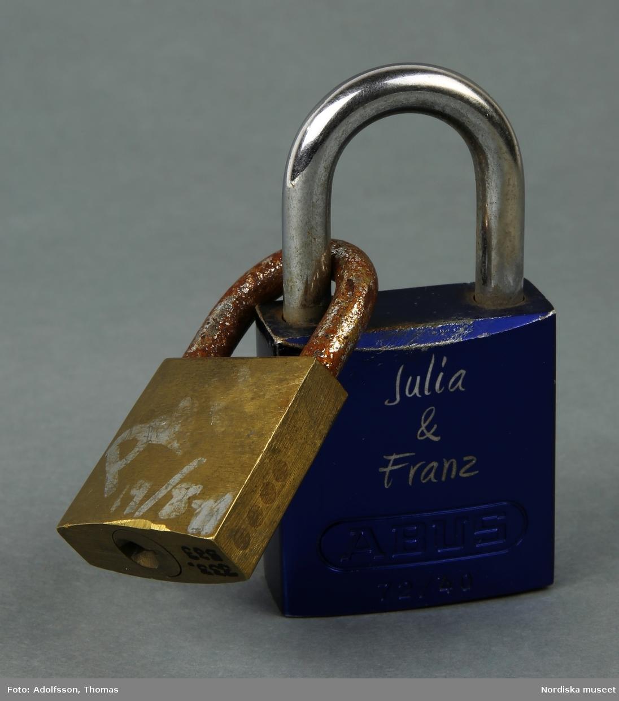 Ett fyrkantigt metallicblått kärlekslås av metall, med initialer inristade på ena sidan. På låset sitter ett mindre kärlekslås av mässing, 3 cm brett med påmålade initialer, datum,och årtal m.m. i silvertusch. /Lena Kättström Höök 2019-01-23