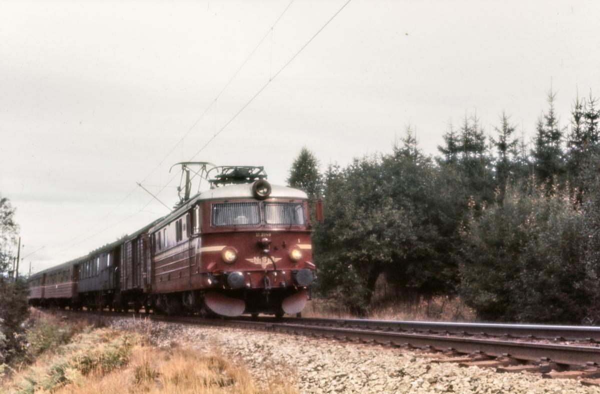 Elektrisk lokomotiv El 11 med persontog fra Gjøvik til Oslo Ø mellom Sandermosen og Kjelsås stasjoner