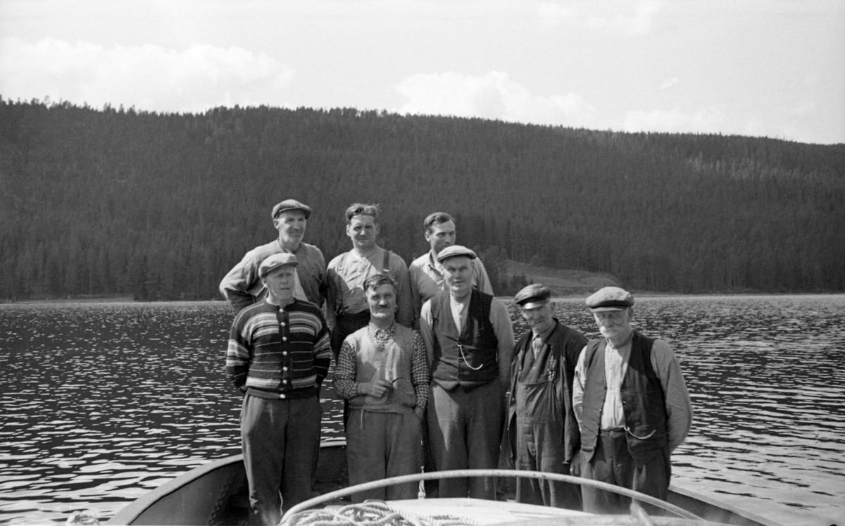 Mannskapet på D/S Storsjø, fotografert i akterenden på båten sommeren 1943.  Mannskapet besto av åtte menn, etter utseendet å dømme fra cirka 40 år og oppover til drøyt 70 år i alder.  De er alle iført arbeidsklær og fem av dem har skyggeluer.  Båten ligger tilsynelatende stille på en sjø med småkruset overflate.  I bakgrunnen ei li med tett barskog, med unntak av et dyrket areal ned mot sjøkanten over hodene til de to karene lengst til høyre på fotografiet.