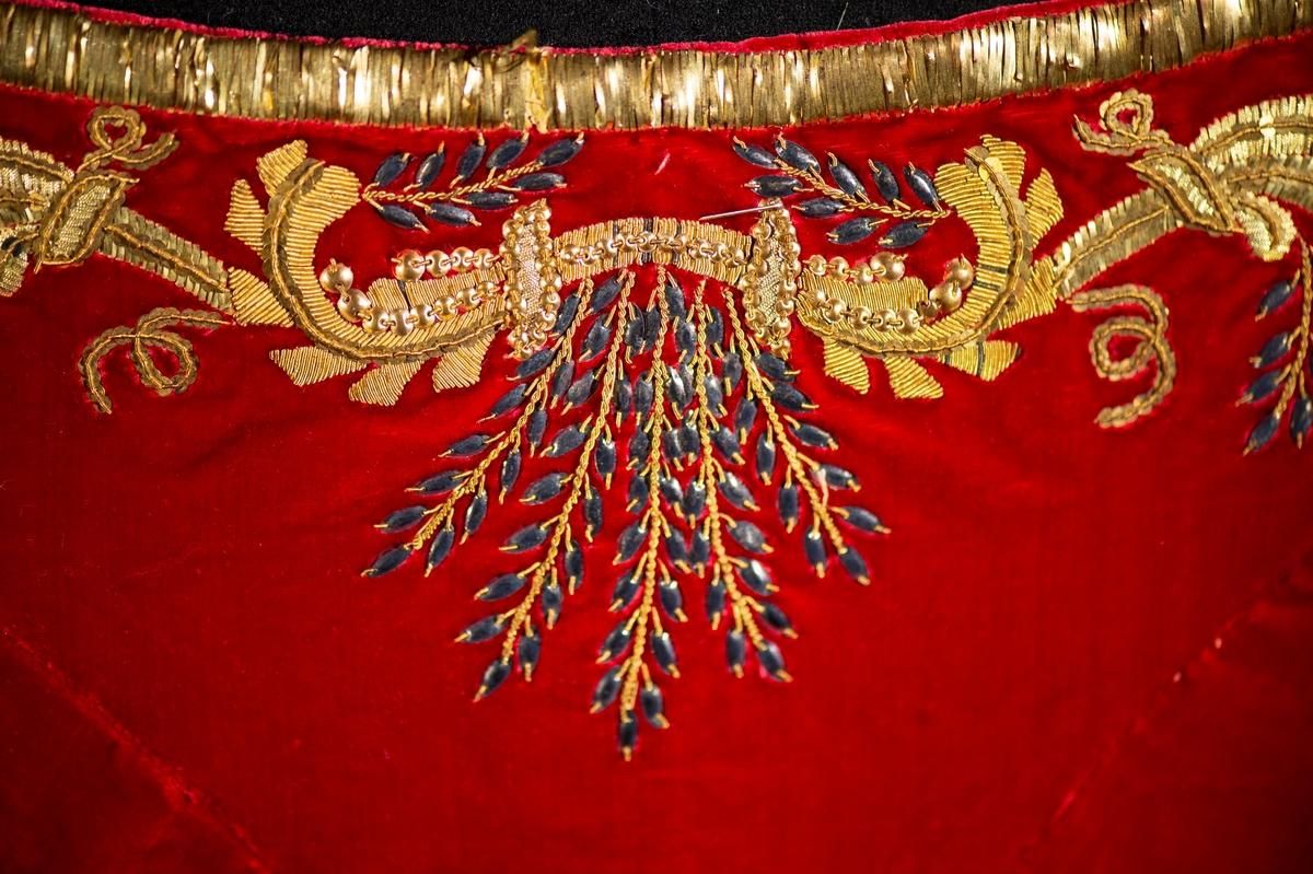 Mantel av röd sammet, rikt guldbroderad. Nr 2 i förteckningen. Liv till hovdräkten av rött sammet med rikligt broderi i guld märkt med . B. Dräktdel - (Oläsligt ord---?) skärm (?) av röd sammet med vita sidenband i ändarna (liksom månskära C. Bred sleif med rikligt broderi i guld röd sammet. D. Livstycket med vita sidenband. E. Något maläten vid (oläsligt ord---?) före inl. till V. museum.