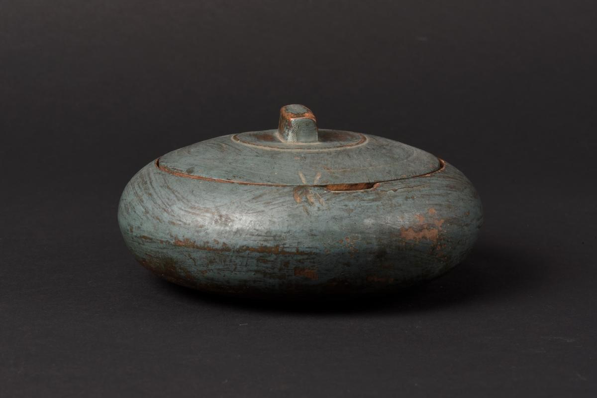 Rund svarvad smörask med lock, tillverkad av ek. Locket har ett rektangulärt utskuret handtag. Smörasken är målad i en blågrön färg.
