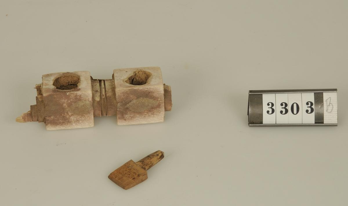 Enligt givarens påskrift kommer byggnadsdetaljerna från ett koptiskt tempel nära Kairo. Templets ålder över 1600 år.  a) En tegelfärgad marmorbit från ett mosaikgolv. Storlek: 5,3 x 2,4 cm. b) Del av ett skulpterat trägaller. Storlek: 10 x 3 cm.  Har tillhört de Adelsköldska samlingarna.