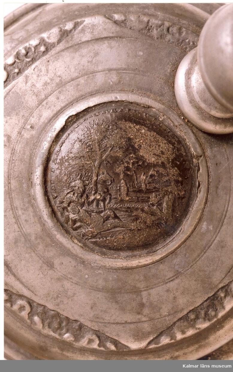 KLM 5725. Krus av fajans. Cylindrisk med grepe och tennlock, vari avbildning av en tysk medalj. På kruset ett landskap med hjort och hund, allt i blått, violett och gult. Tumgrepp: kula med gördel och krönknopp. Tennskodd botten. Tillverkat i Tyskland.