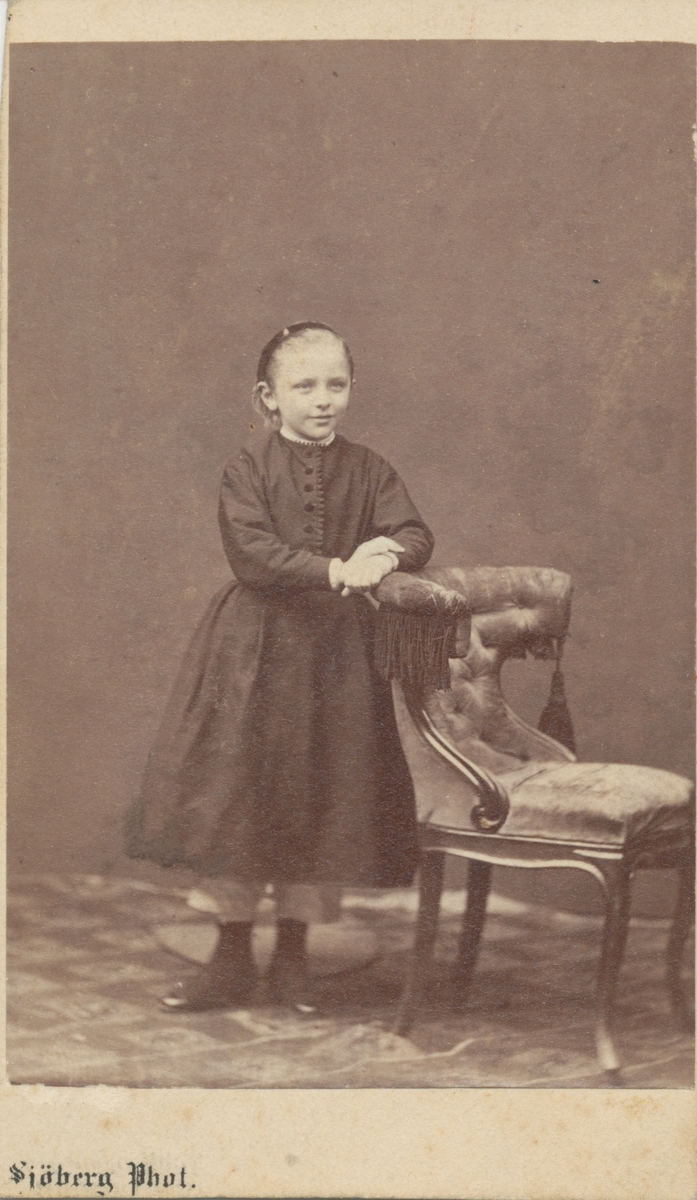 Lulli Rettig, ståendes vid en stol i studio. Robert och Adelaide Rettigs dotter.