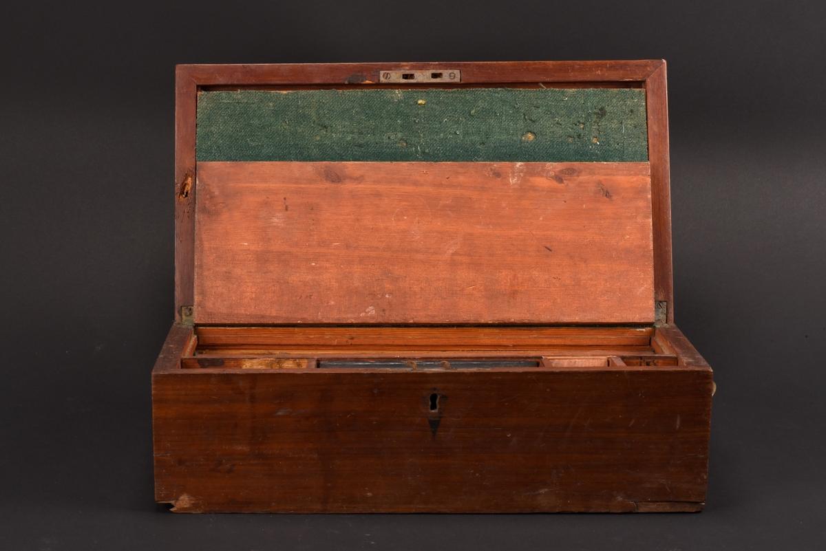 Rektangulärt reseschatull tillverkat i furu med mahognyfanér. På sidan finns en utdragbar låda som är indelad i flera fack. Innanför locket finns ytterligare ett uppfällbart lock, klätt med grön filt som bildar en skrivbordsyta. Därunder indelning med fyra fack.