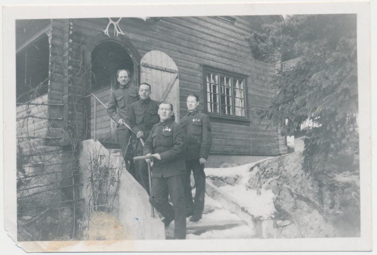 4 voksne menn i militæruniform foran hytta til Lars og Olga Mørk på Langebåt, ukjente