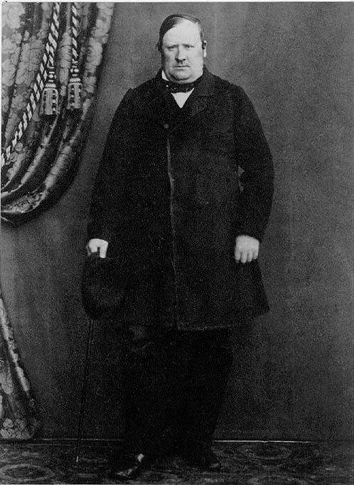 Porträtt av rådman Sven Johan Petersson i Gränna, i helfigur. Han står med en hatt och käpp i höger hand.