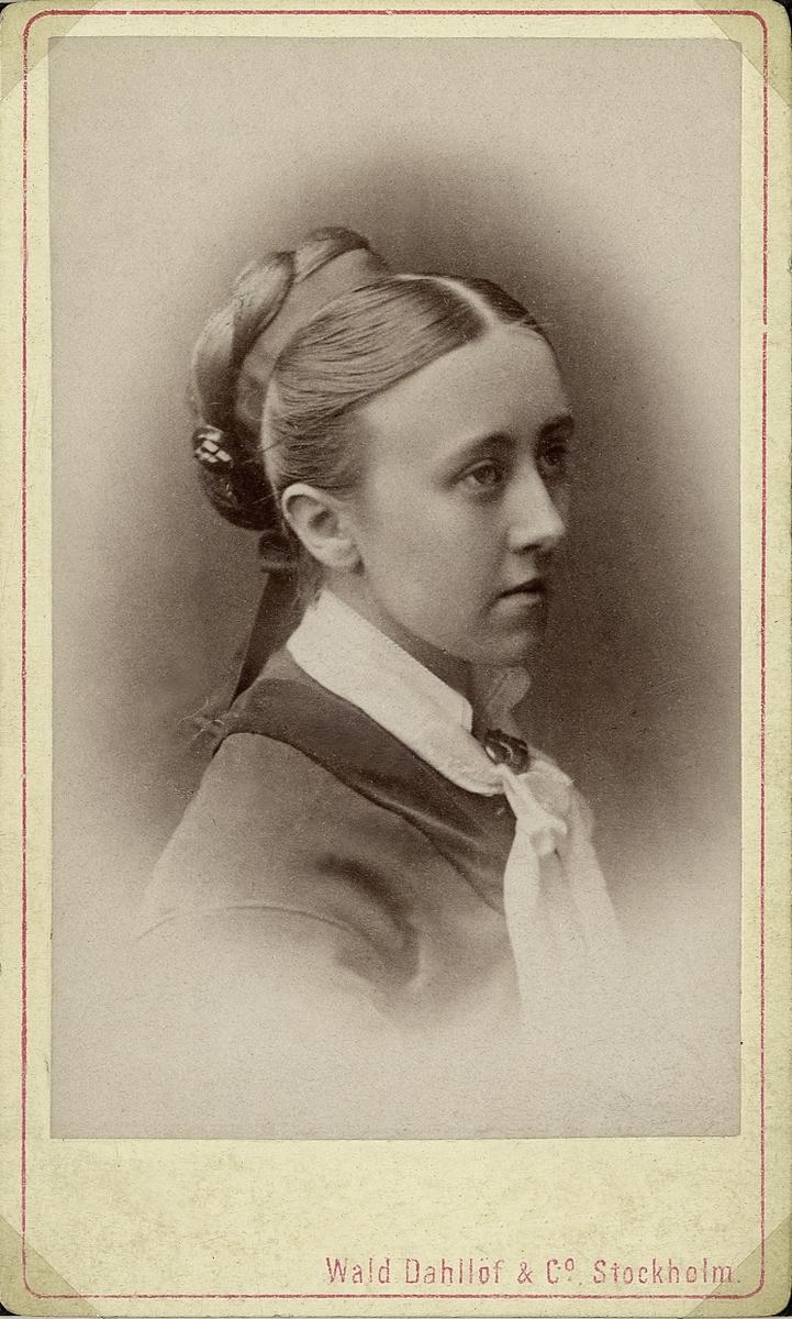 Porträttfoto av en kvinna i klänning med sammetskrage och en vit halsduk. På halsduken syns en brosch.  Bröstbild, halvprofil. Ateljéfoto.
