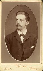 Porträttfoto av en ung man med mustascher, klädd i mörk kava