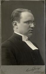 Porträttfoto av en man med glasögon, klädd i prästrock med p