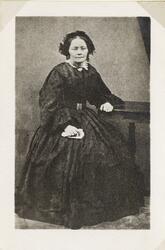 Porträttfoto av kvinna i mörk krinolin med mörk hårklädsel p