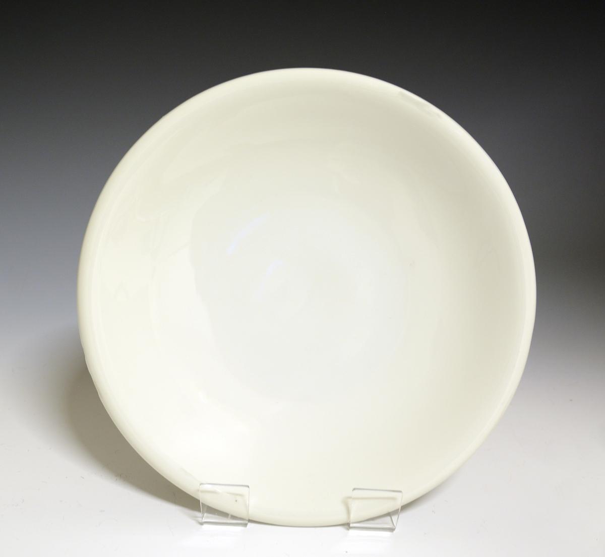 Prot: Litet fat av porselen, med glatt, nedbøyet kant. Hvit glasur. Tilhører servise 1847.