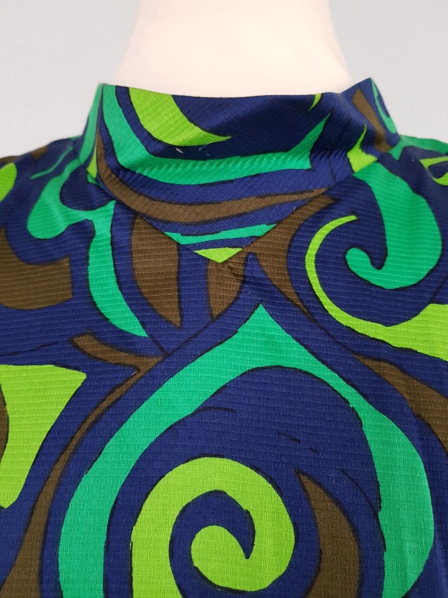 Knekort penkjole med V-ringning, utfylt av en lav, stående linning i halsen og trekvartlange, trompetformede ermer. Nederst på ermene stor splitt i ermsømmen, og høy fald, slik at det kan se ut som om ermene skal være oppbrettet i nederkant. Blankt materiale med stripet struktur i veven, påtrykt spykedelisk mønster i blått og grønt, der syrlig grønt dominerer. Innsvinget ved hjelp av panelsømmer på forstykket, og lukket med glidelås midt bak. Et lite innsnitt på hvert ryggstykke, fra skuldersømmene. Helfôret med fôrsilke. Ingen varefakta. Str. 40.