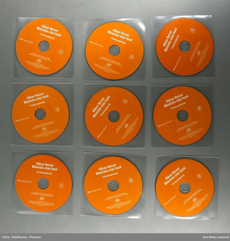"""CD-bok.  a:1-2-n:1-2) 14 st CD-skivor, i en kvadratisk, transparent plastficka, innehållandes uppläsning av romanen """"Människa utan hund"""" skriven av författaren Håkan Nesser som även är uppläsaren på denna CD-inspelning.  Inspelningen är totalt 15 timmar lång.  CD-skivorna är tunna cirkelfornade,  12 cm i diameter, på ena sidan oranga med text om titel samt kort om produktionen. Varje skiva är numrerad för att visa rangordningen i vilken skivorna ska lyssnas på/spelas. Baksidan på skivan är silverfärgad, speglliknande, och innehåller själva ljudspåren som läses av när skivan placeras i en CD-spelare. Varje skiva är separat plackad i en kvadratisk, transparent, plastficka för att skydda mot repor som ev skulle kunna skada skivan.  Samtliga skivor är tillsammans packade i en o) kvadratisk papperskartong/ konvolut. Konvolutet har på framsidan en bild av ett fönster med ett gultonat fotografi visandes ett fönster med en flaxande fågel utanför. På konvolutets baksida finns en introduktion till bokens handling samt  information om tillverkningen av denna CD-bok. (CD är en förkortning av engelskans Compact Disc. CD-skivan kan lagra digital information, exempelvis musik. CD skivans konstruktion: överst är ett transparant plastlager följt av ett tunt lager av blank metall med ett präglat spiralformat spår med mikroskopiskt små gropar som avläses av CD-spelarens laserstråle när skivan snurrar (ca 500-700 varv/minuten). Ljuset studsar tillbaka och läses som en följd av ettor och nollor, som i detta fall, blir till ljud.(Källa/. Nationalencyklopedin)   /Cecilia Wallquist 2019-02-20"""