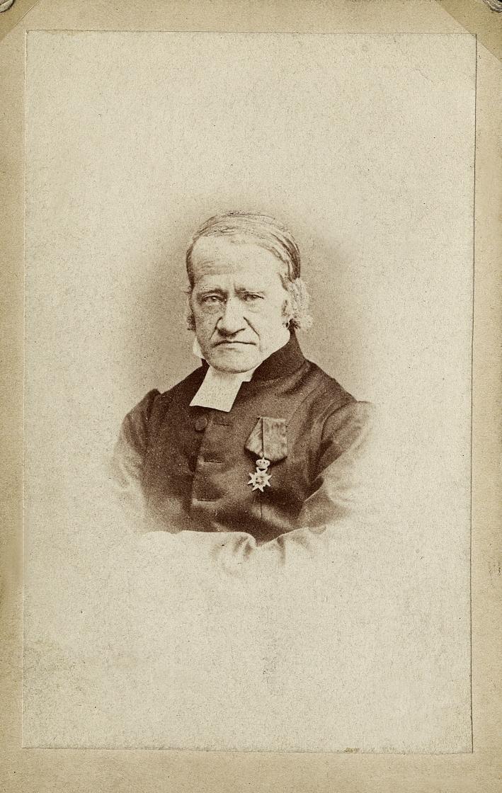 Foto av en äldre man med polisonger, klädd i prästrock med prästkrage. På bröstet syns Nordstjärneorden.  Bröstbild, halvprofil. Ateljéfoto.