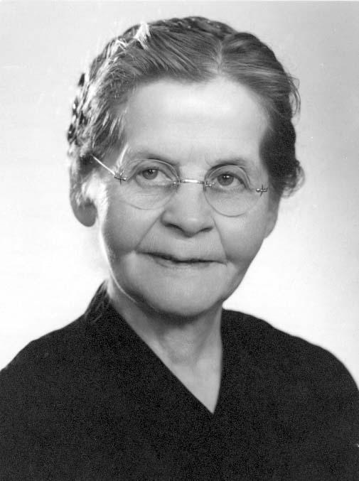 Porträtt av en äldre kvinna med runda glasögon.