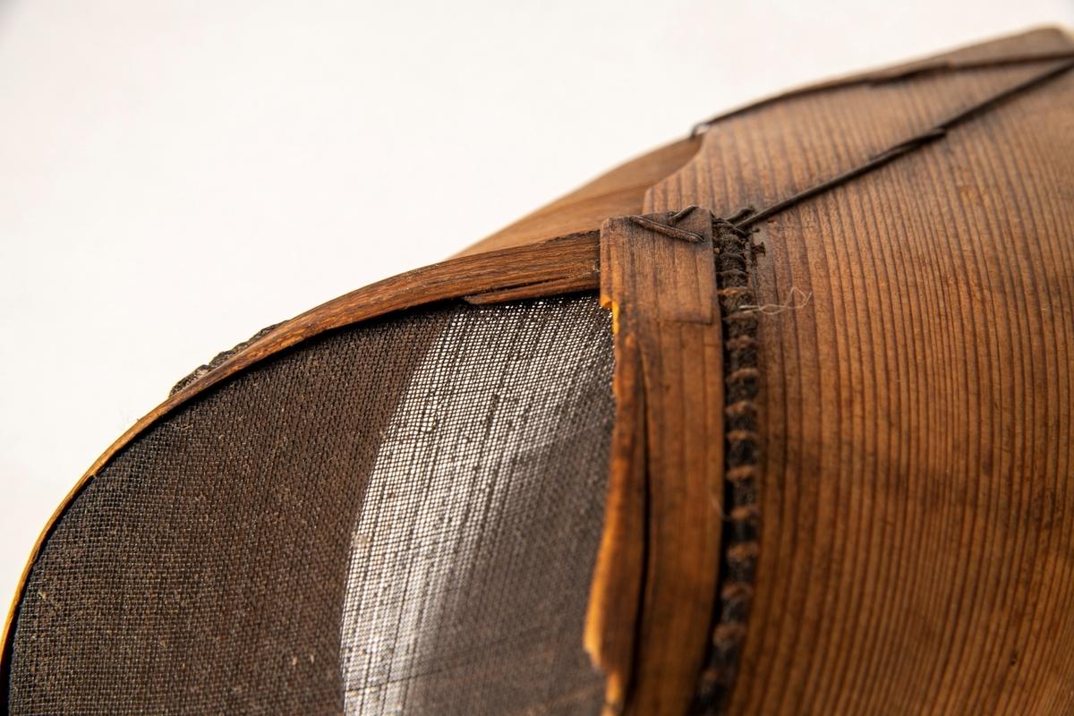To melsikter av et bredt finerbånd som er bøyd opp i snipp, slik at sikteduken blir dråpeformet. Sømmen pent oversydd med stårltråd.