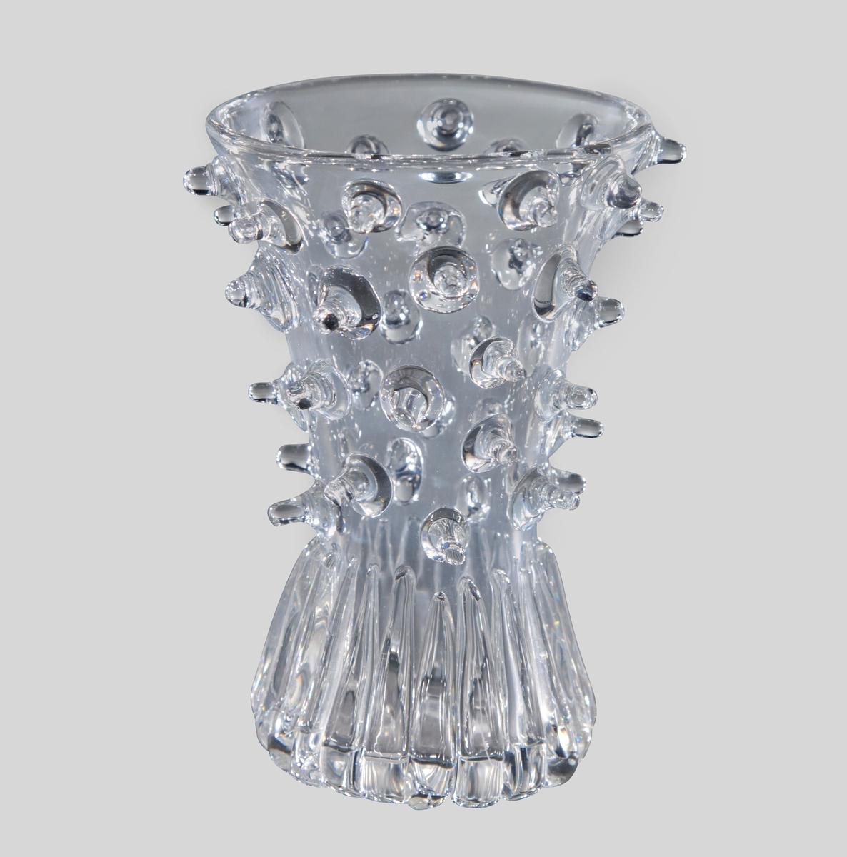 """Begerformet vase i klart glass. Øvre del av er tett dekorert med plastiske """"nupper"""" som stikker ut fra korpus, mens nedre del har dåpeformede vertikale riffler i lavt relieff."""