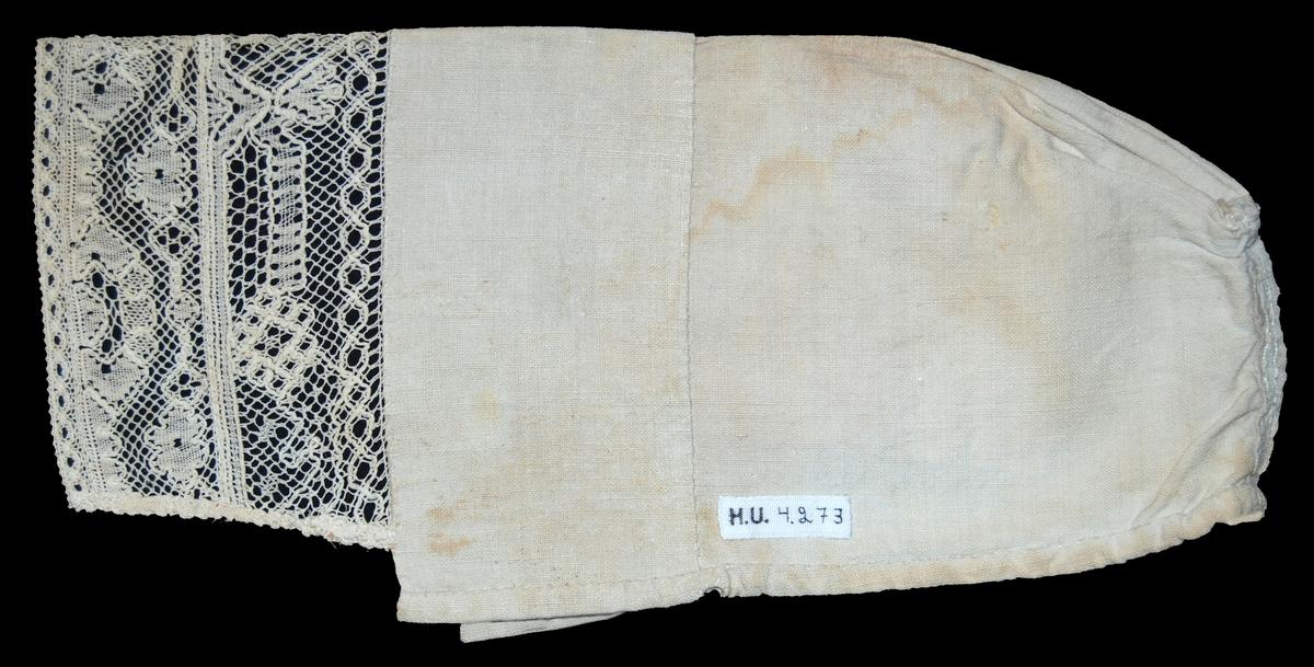 Av  1/2 blekt linnelärft, rakt stycke med söm mitt bak, hoprynkad ovanför sömmen, 2 st kantsydda hål vid nederkanten. Bred fåll vid framkanten.  Kantad med spets, sammanfogad av 3st spetsar, den yttre smalast.  Spetsen kortare än hattens framkant. Pappersetikett med tryckt och med bläck skriven och blyerts skriven text: Gestriklands hemslöjdsförening spettsutställning, Gävle 1916. Mockfjärdshatt. Nederst tulipanaros.