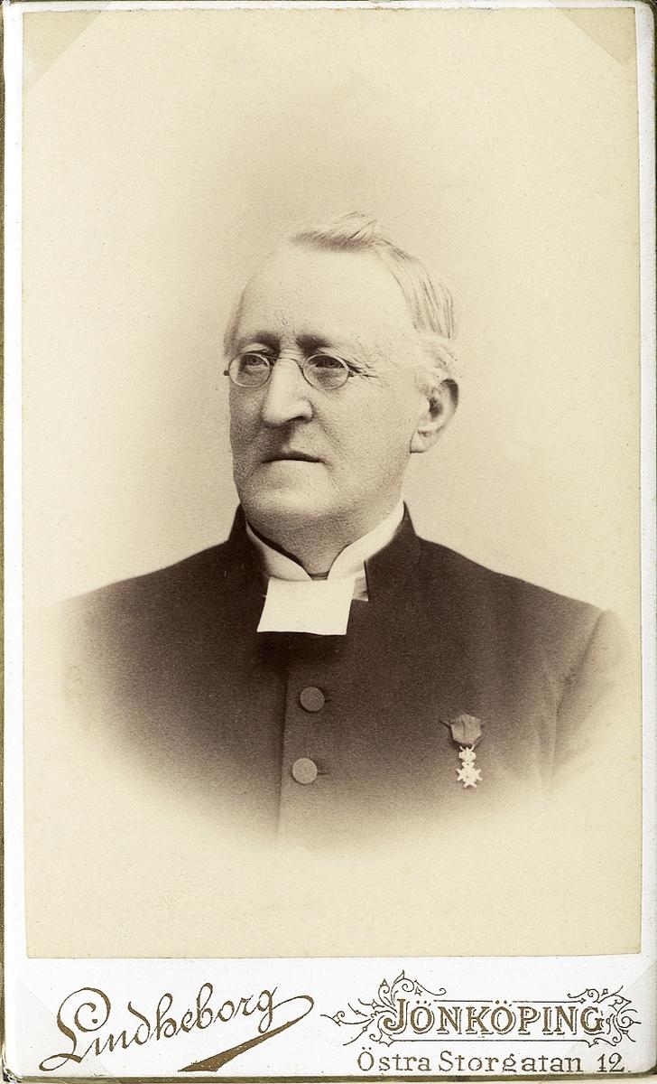 Foto av en äldre man med glasögon, klädd i prästrock och prästkrage. På bröstet syns Vasaorden.  Bröstbild, halvprofil. Ateljéfoto.