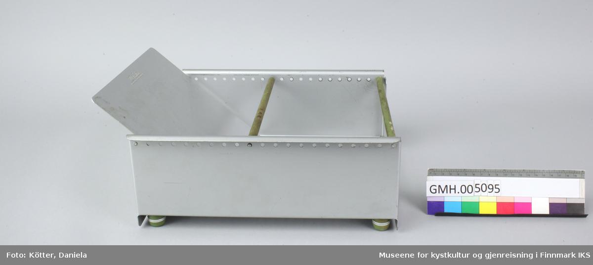 Trauet har en bunn og to sider av aluminium. Sidene er foran og bak forbundet med stenger. Imellom er det en stang som kan flyttes Det følger også med en skillevegg som kan settes i slisser i bunnen.