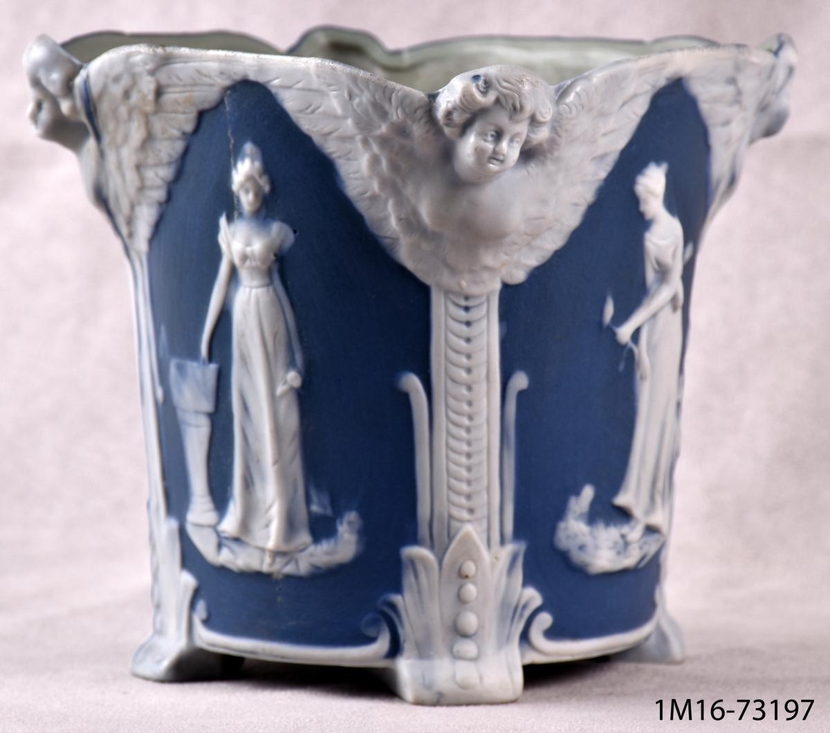 Urna för blommor, rund nedtill, upptill fyrsidig med fyra fält med kvinnofigurer, dekor i ljus- och mörkblått.