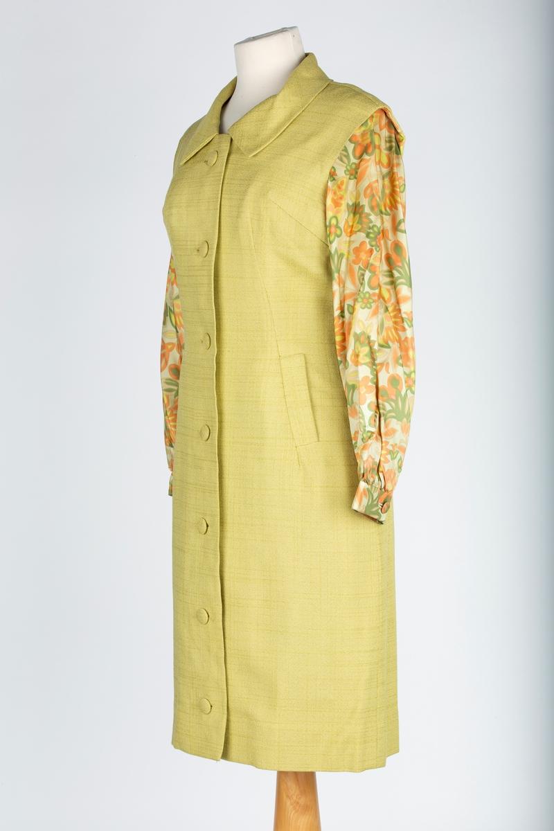 Kjole med ermeløs jakke/kåpe  A:  Kjole Lange ermer med mansjett. Buet halsringning forran,  dyp rigning i rygg. Høyt buet liv me 2 par loddrette brystsnitt, og 2 ryggsnitt. Metallglidelås i ryggen. Glatt smalt skjørt i 3 bredder, innsnitt Mangefarget stoff i grønne orange nyanser. Bortsett fra ermer er kjolen foret. Svettemerker ved halsringing og mansjetter  B: Kåpe Kåpen , ensfarget lindegrønt stoff i linstrruktur. 4 bredder. krage. uten ermer. knappes forran med 7 trukne knapper av kåpestoffet. Forran skrått lengdesnitt og brystsnitt.  Stikklommer i innsnittet. Lengdesnitt i ryggen- Foret med samme stoff som kjolen. Lengden justert for hånd  Kjøpt i Holland 1969, forsinket bryllupsteise.   Kåpen er merket med str. 40.  Brukt rundt 1970         .