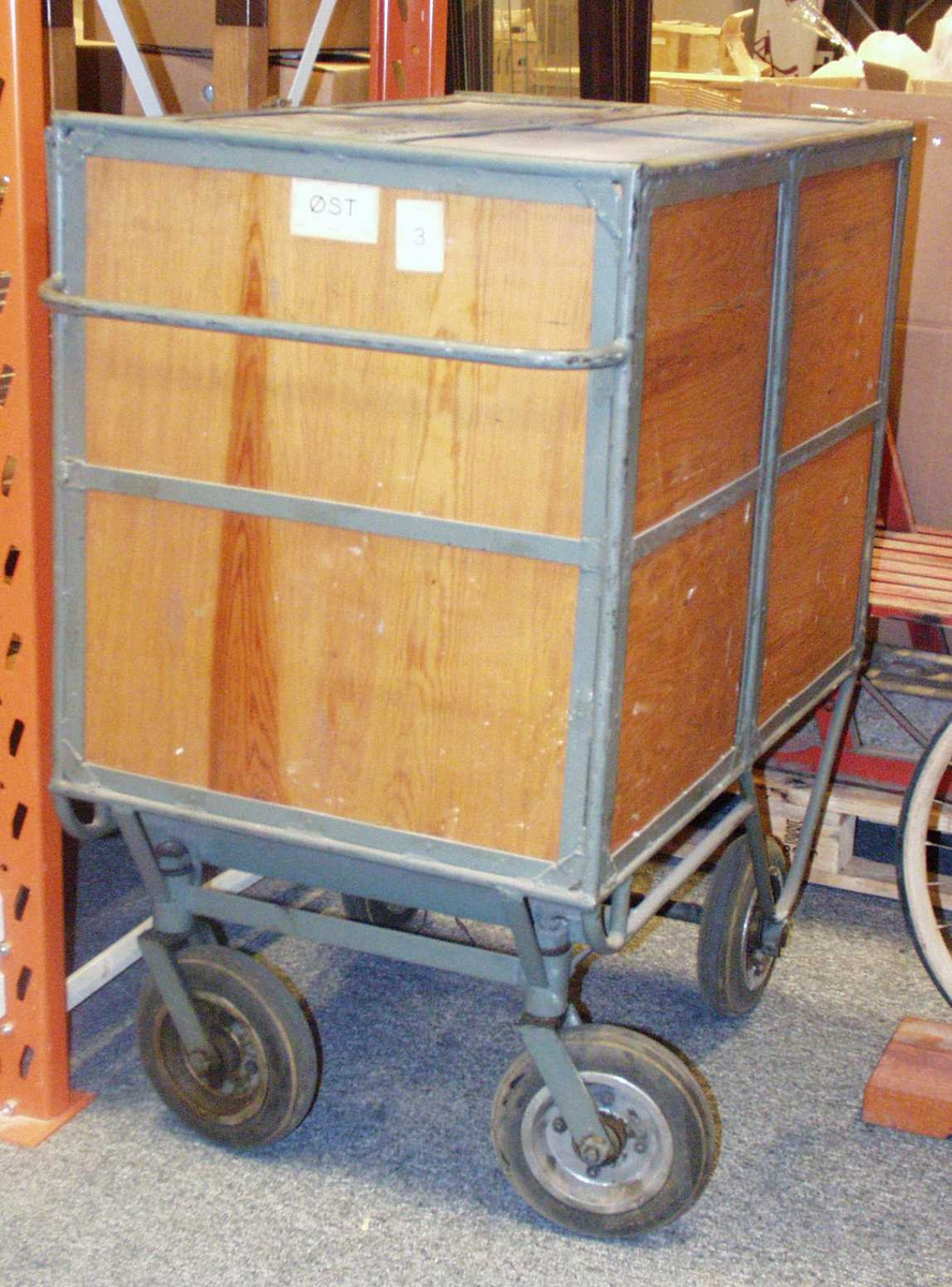 En tralle i tre med fire hjul. Den er låsbår og har et lokk øverst.