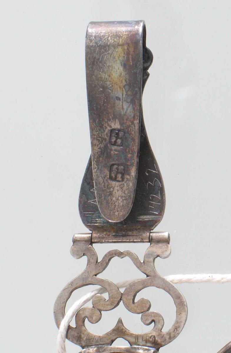 Belteanheng, m.nøsteholder  og nålehus.  Håndarbeidsredskap i sølv, elfenben, mahogny, sølvplett.    a) Beltespenne med rokokkokartusj, på baks. stemplet to ganger ER i rektangel.  Fra spennen henger elfenbensspole  i buet og knekket holder, fra spoleendene  to nålehus el. lign i sølvplett.  I kartusjen initialer   EC  = Elisabeth Charisius, f. Cooper, (1757- 1791
