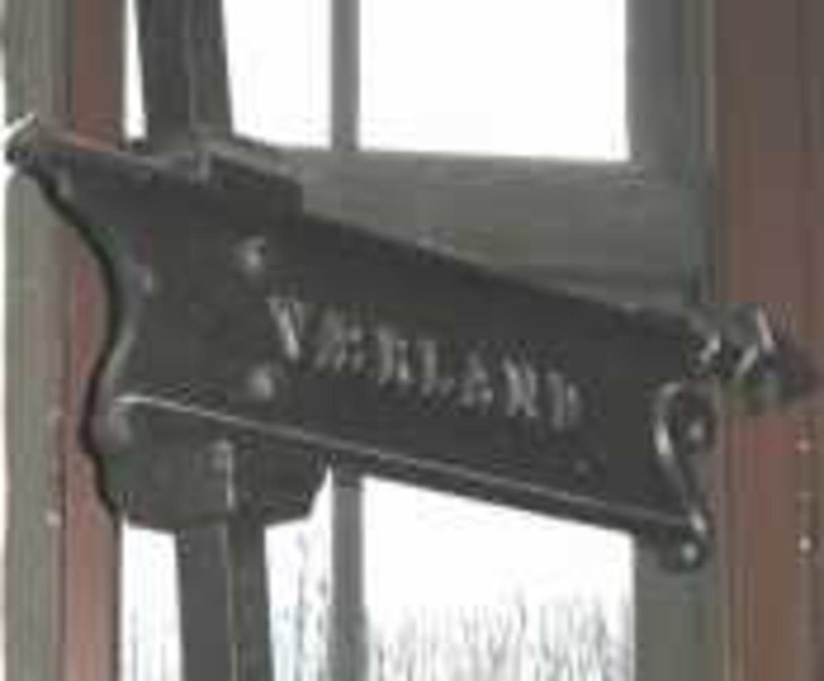 Stolpe  m  henvisningsskilt med tekst Værland. Selve skiltet er elegant utformet med enkel akantuspynt i begge ender. Skiltet er skrudd fast i stolpen. Kule på toppen av stolpen mangler.