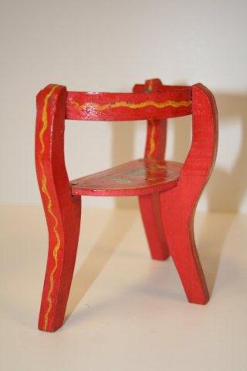 Trebeint benk. Halvsirkelformet sete av finér. Ben og stolper i étt. Kombinert armlene og ryggstøtte i metall som er malt som resten av stolen. Rødmalt  med blomsterdekor i gult, grønt, hvitt og blått. Streker og kanter er malt på.