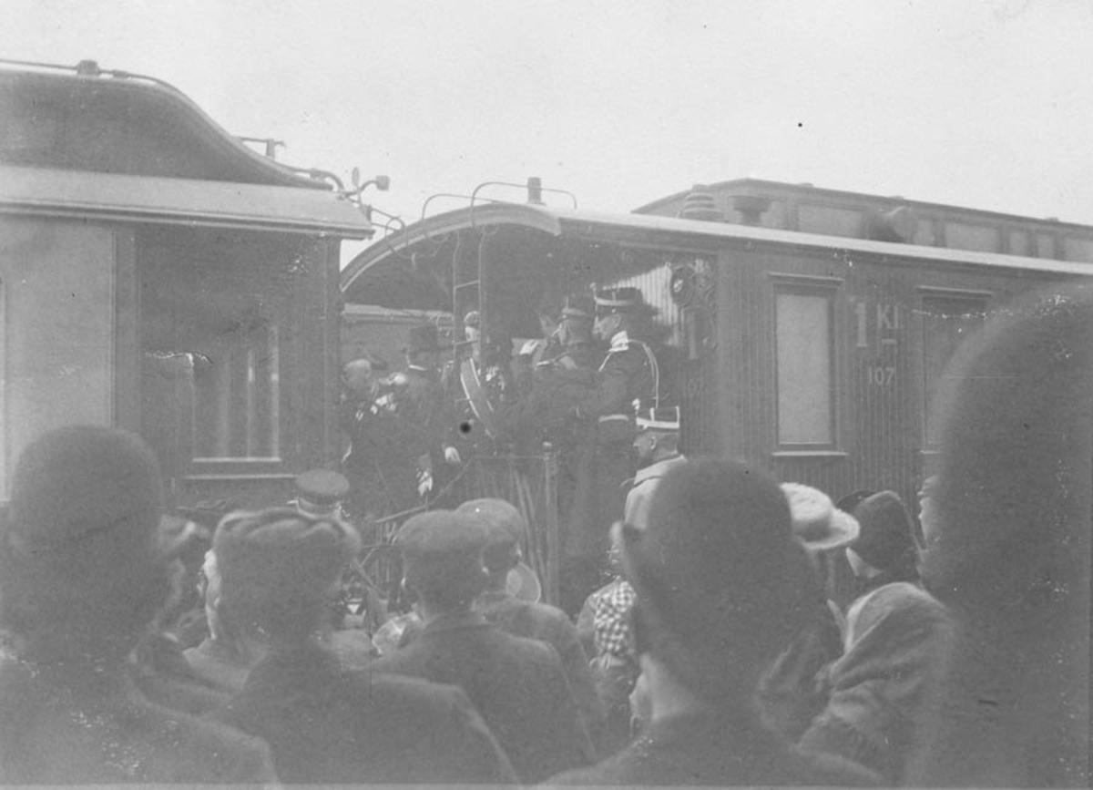 Mennesker på perrongen, offiserer på jernbanevogn