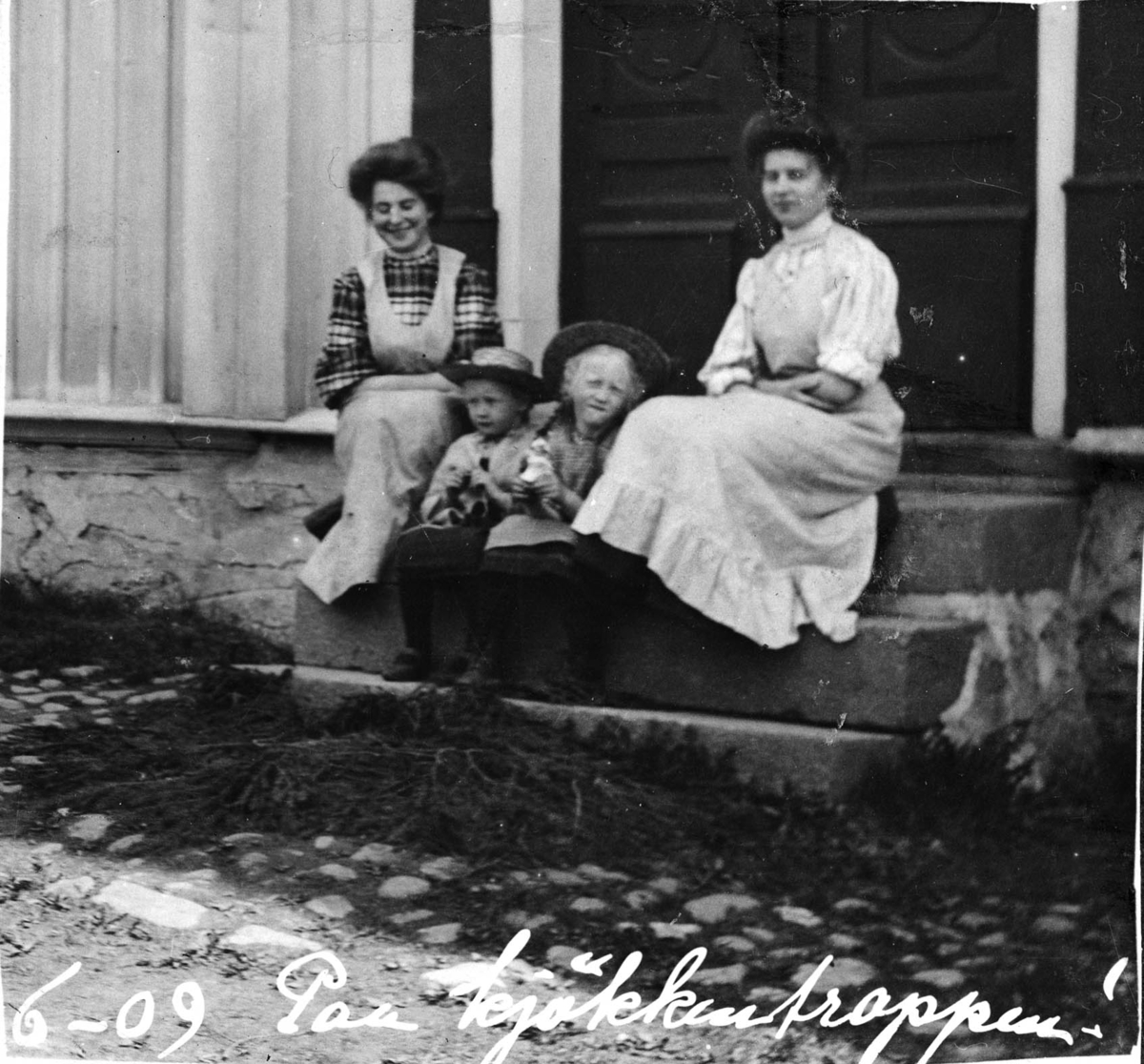 To piker og to voksne kvinner på en trapp, hushjelper