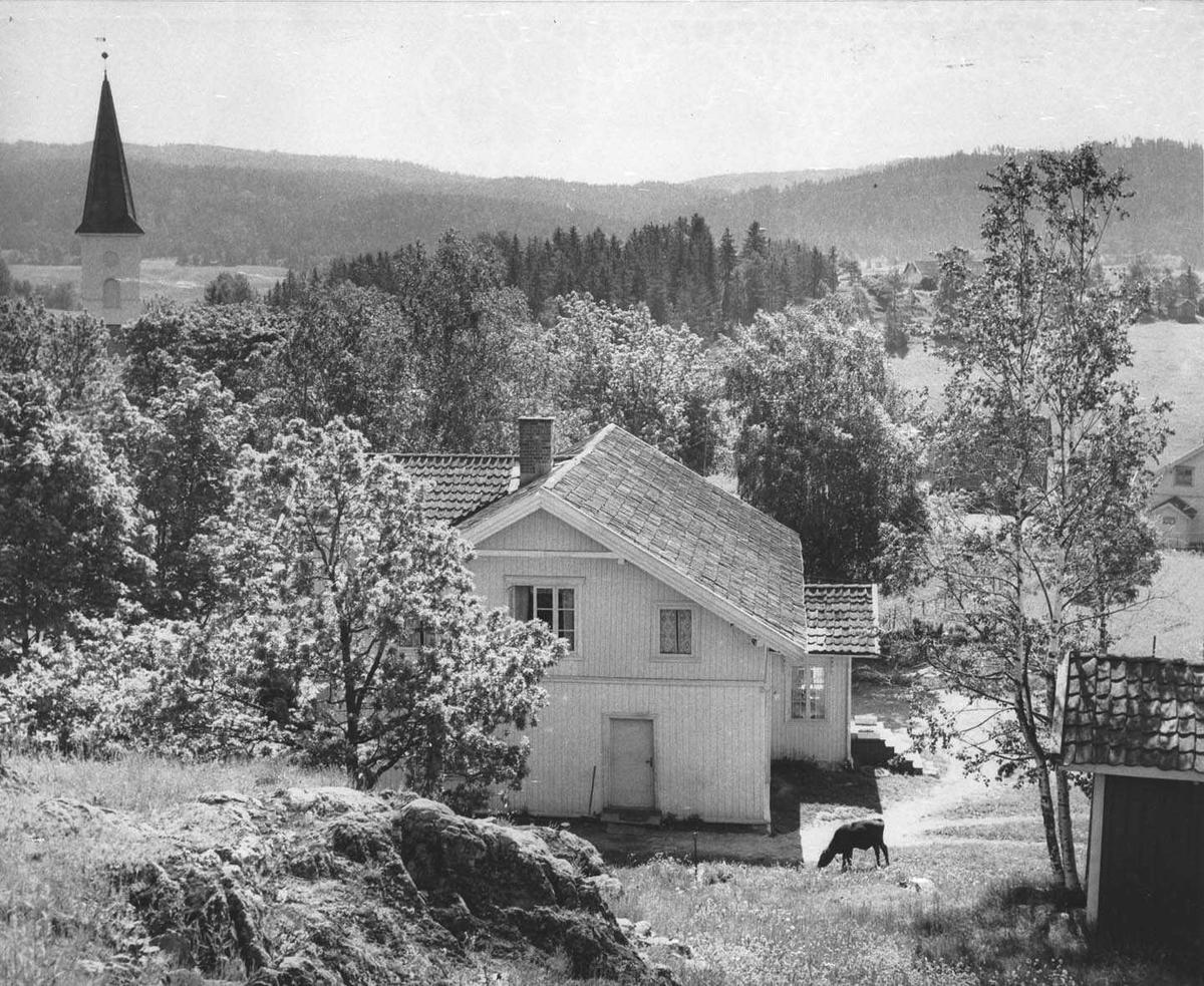 Våningshuset på Hammer søndre gård. Spiret på Lørenskog kirke.