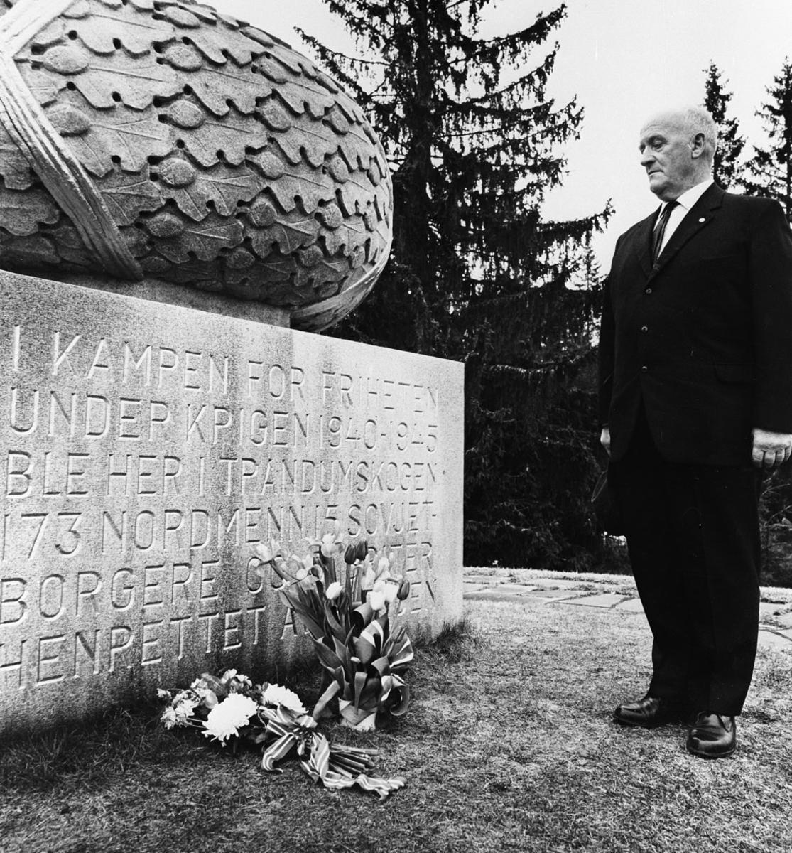 Olaf Linnerud foran minnesmerke over dem som ble henrettet på Tranddumskogen.