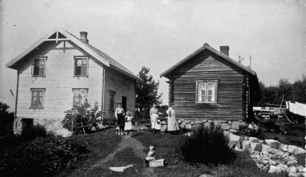 Kvinner og barn utenfor hus.