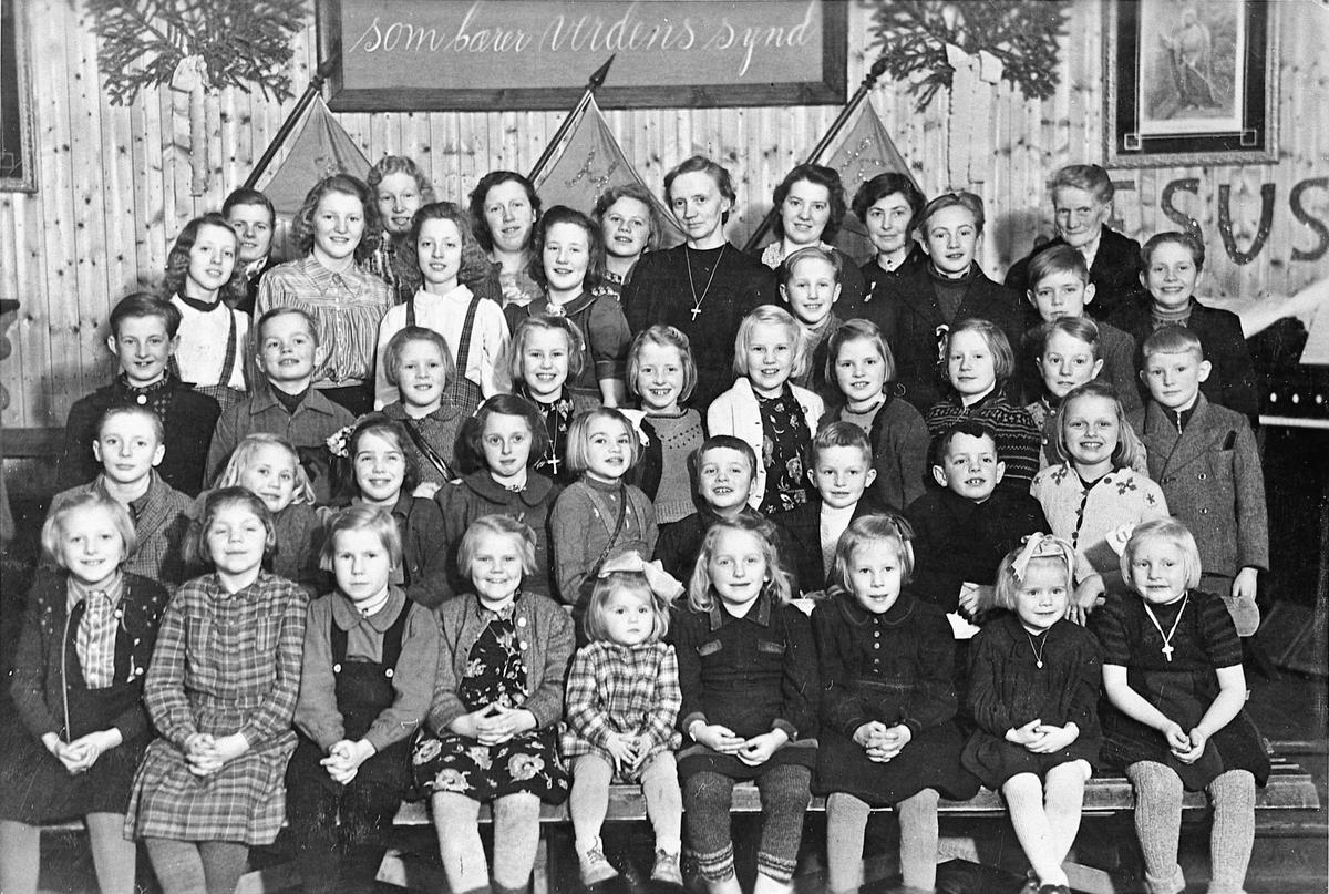 """Betania, Gullverket. Søndagsskolen. Ca. 1945. 1. rad fra v.: X, Aud Hansen, Marit Nyberg, Kirsten Olsen, X, Brit Røen, Ragnhild Tjernsmo, Berit Solberg, Evy Storbråten. 2. rad fra v.: Odd Sjøberg, Bjørg Lien, X, Målfrid Røen, Åse Sandholtbråten, X, X, Willy Holm, Berit Karlsen. 3. rad fra v.: Øygard Storbråten, X, Reidun, Eva Olsen, Rakel Holm, Ester Olsen, Bjørg Holm. 4. rad fra v.: Ruth Sjøberg, Hoelsether, Ester Sjøberg, Irene Stenerud, søndagsskolelærer Ester Røen, Annar Stenerud, Roald Storbråten, Kai Sjøberg, Åge Nilsen. Bakerste rad fra v.: Eva Solberg, Petra Storbråten, Kari Fjellberg, Lien, Hoelsether, Signe Vangen, Johanne Røen.  12.11.2012 Fullstendig navneliste finnes på side 95 i boka """"Lokalhistorie nordre og østre Gullverket"""" av Henry Halvorsen og Trond Øivindson Lunde (2001. Skrevet av: Jan Arne Sandholtbråten"""