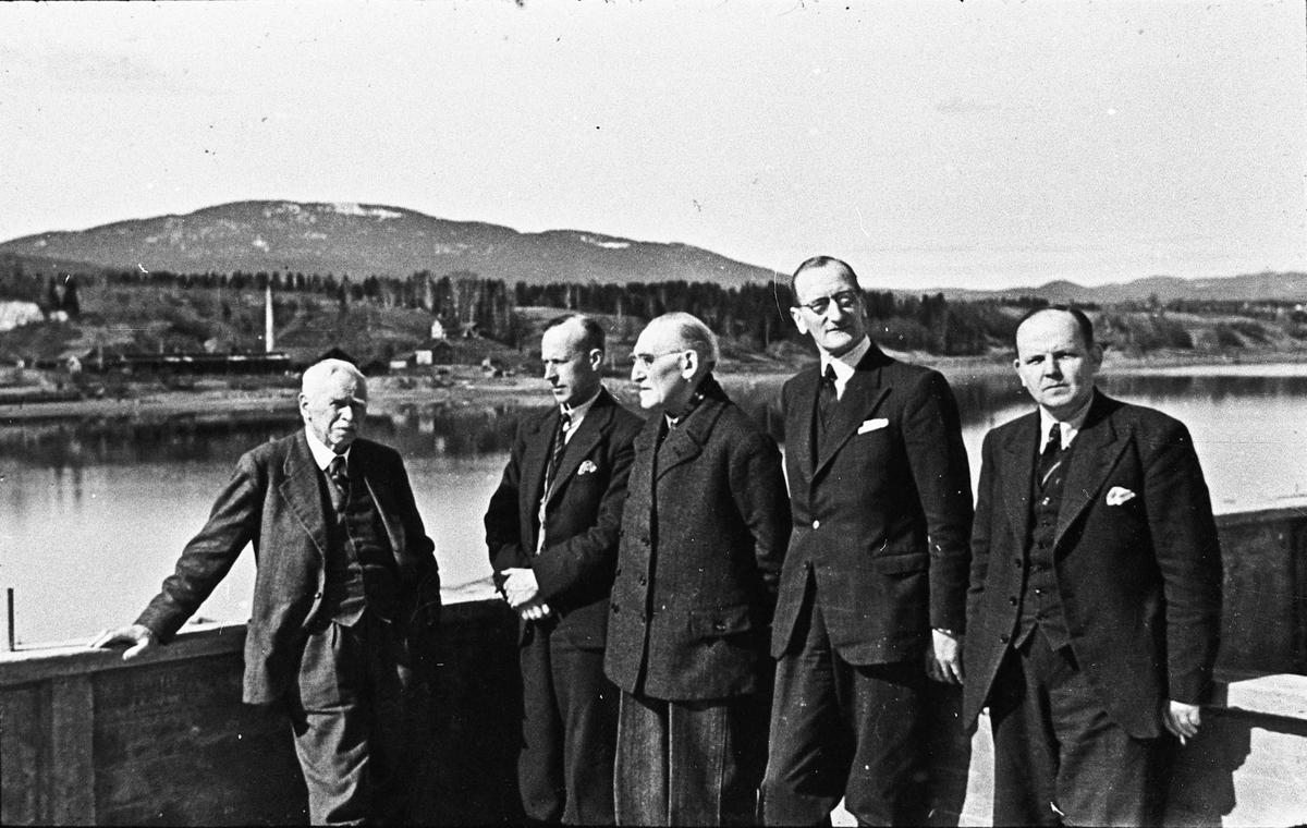 5 menn i en båt på Vorma. Teglverk - og Mistberget - i bakgrunnen.