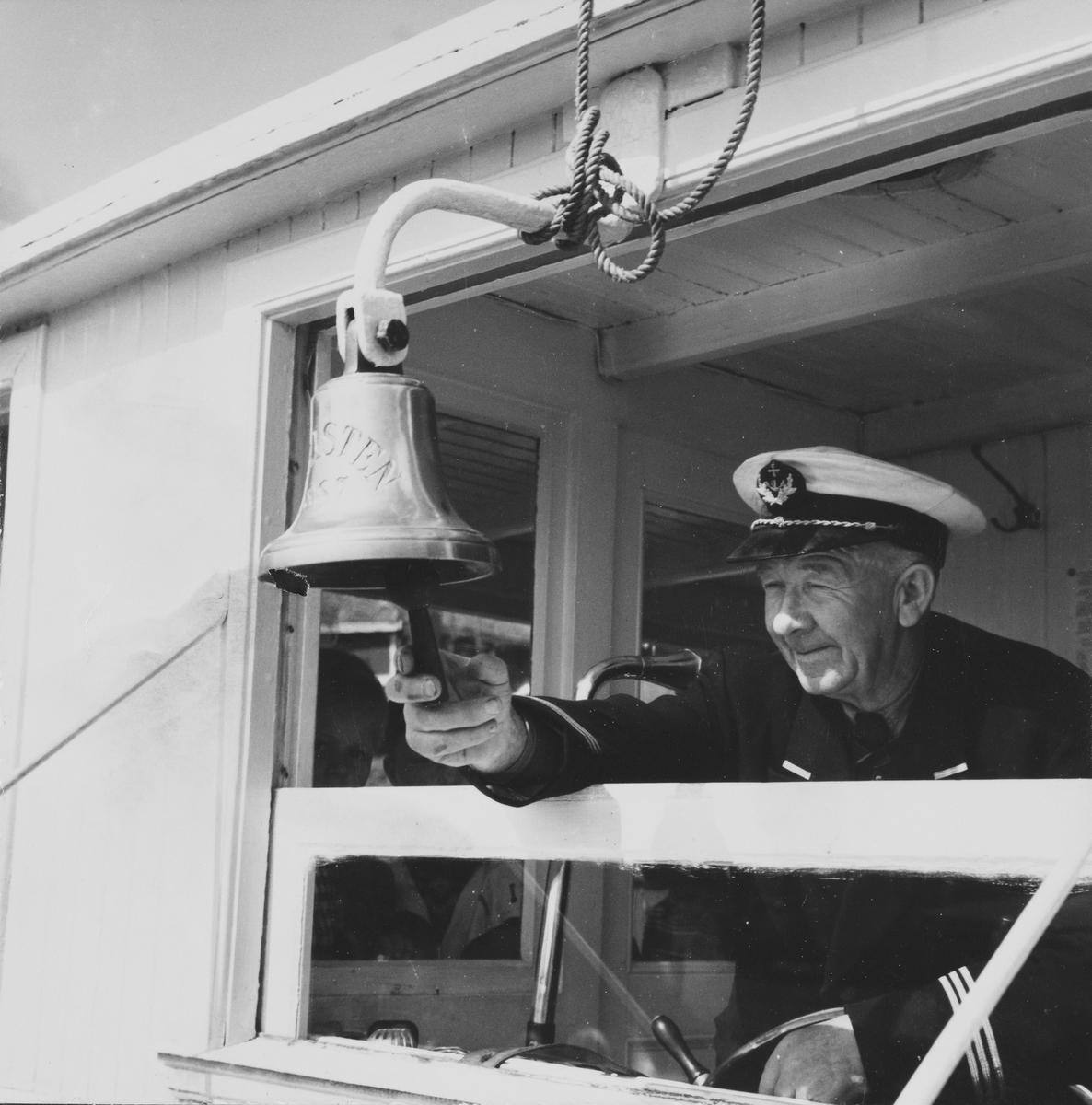 Kapteinen ringer i skipsklokken ombord i D/S Turisten
