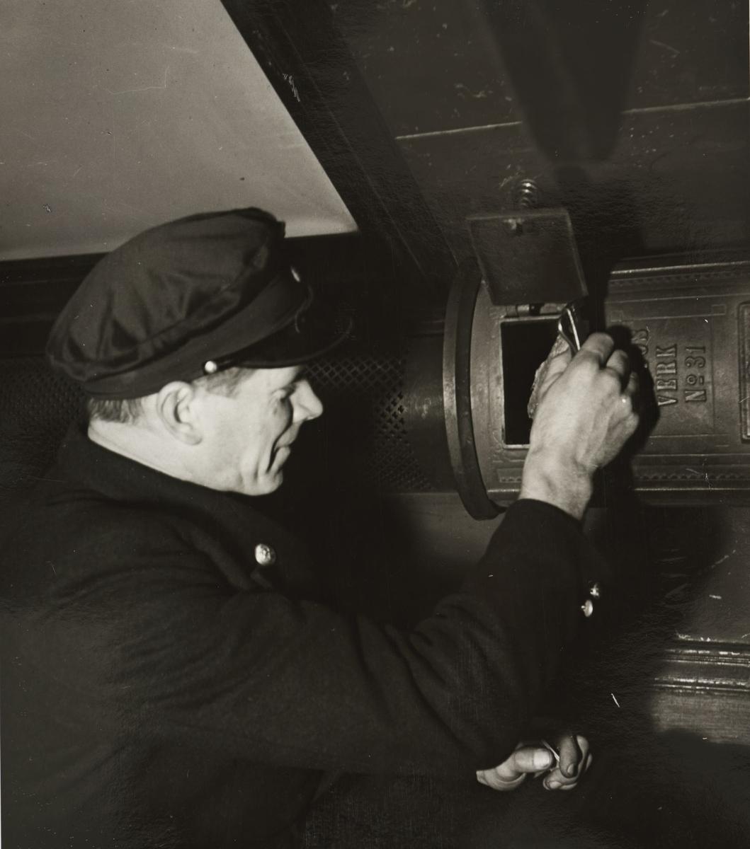 Vogn BCDo7 - interiør. Verkstedarbeider Johan Moseby fyrer i ovnen.