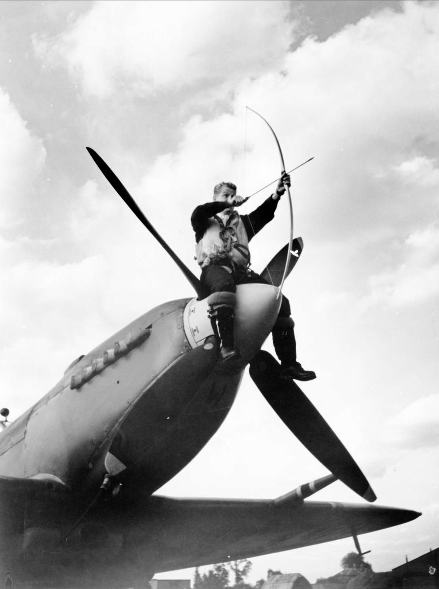 "Den originale bildeteksten lyder: ""Bueskytning er en meget populær idrett blandt flygerne på de norske fighter squadrons i England. Det er pussig å se med hvilken glød flygerne går opp i konkurranser med dette eldgamle våpen, disse folkene som er vant til tidens mest moderne ødeleggelsesredskap."""