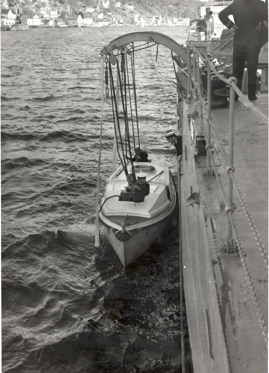 KNM Tromsø. Motorbåten skal heises opp.