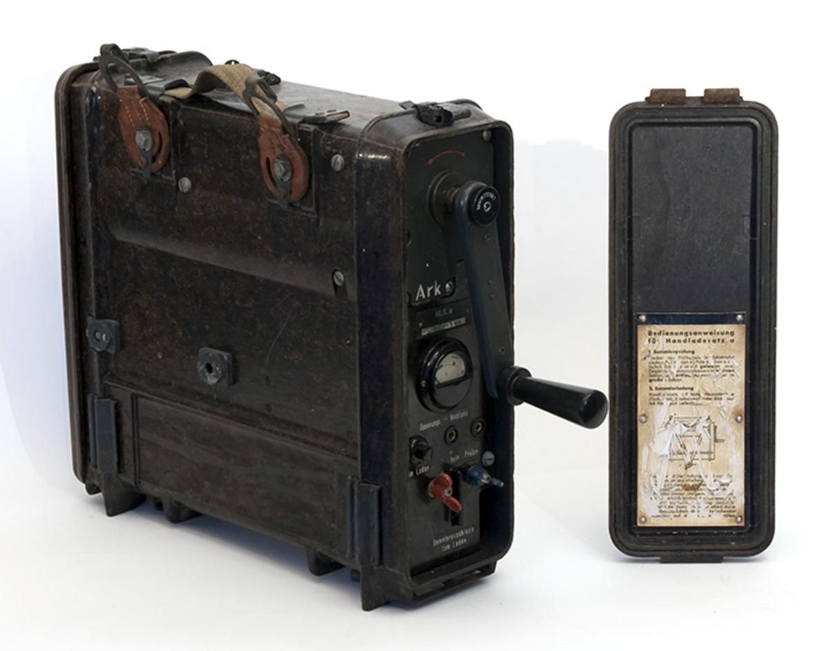 Transportabel generator med sveiv, to kabler. Tyskprodusert, antagelig fra 2. verdenskrig. Til radio og telefonsamband. Tysk bruksanvisning på sidelokk.