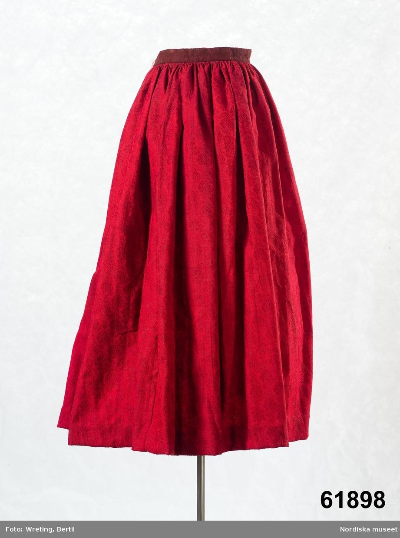 """Kjol i rött ylle av kamgarn med invävt blommönster, 6 våder, framvåden som dolts under förklädet består till övre delen av oblekt linnelärft och har upptill 4 lagda veck och ett sprund. Bakvåderna rikt rynkade mot midjelinning av rödbrunt redgarnstyg infodrat med rosa linnelärft, 2 stora knapphål i linningen vid sprundet för knytband. Bildtext till Nyle´n; Folkdräkter plansch 5, Dräkt från Östra hd: Högtidsdräkt från 1800-talets början. Både livstycke och förkläde av mönstrade sidentyger och kjolen ett dyrbart mönstrat ylletyg..."""" Ett dyrbart köptyg i hög kvalitet, troligen importerat.  /Berit Eldvik maj 2006"""