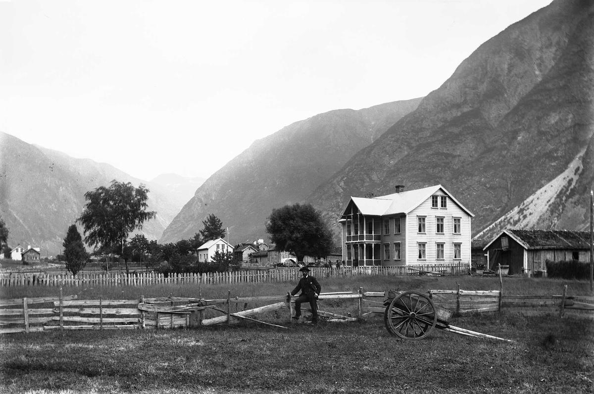 Blaaflat hotell og kyststasjon i fjell- og dallandskap. Mann lener seg mot gjerde, foran står en kjerre.