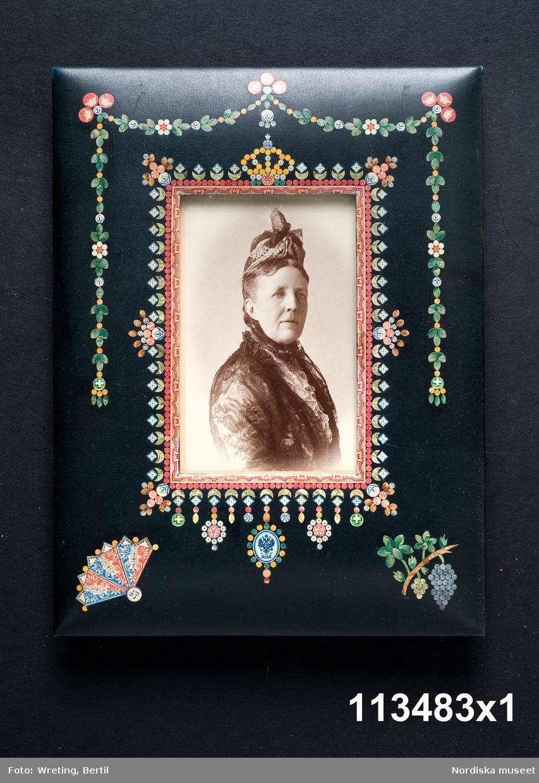 """Huvudliggaren: """"a-å Skrivbordsuppsats, 25 olika pjäser, däribland lampa, ljusstake m.m. allt ornerat med frimärksklipp. Jämte 4 mindre lådor med lösa frimärksdelar. Gåva 17/5 1909 av fru Augusta Cronholm f. Bratt, Birgerjarlsgatan 18, Stockholm."""""""