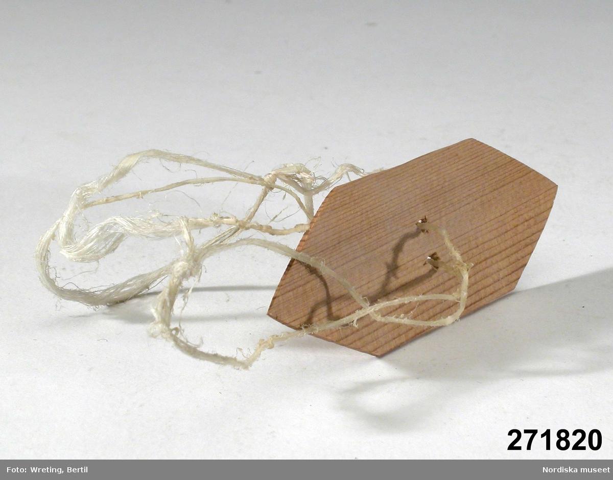 """Huvudliggaren: """"Leksak, ljudleksak, bestående av liten tunn träplattamed spetsiga ändar; en dubbel sentråd genom hål i mitten bringas att rotera och därigenom 'surra'. Tillv. av givaren som modell för att visa en av leksakstyperna från hans barndom. G 28/6 1964 Renägare Anders persson Blind, Arjeplog."""""""